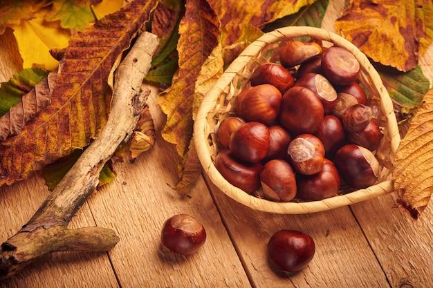 ボウルに栗を馬に乗せ、木製のテーブルに黄色の葉を落とします。秋の背景。