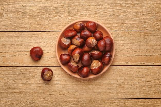 木製のテーブルのボウルにセイヨウトチノキ。秋の自然の収穫。コピースペースのある上面図。