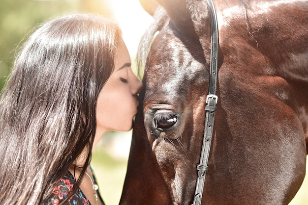 Horse and girl share an emotional moment in close up shot as they appear to kiss. face to face. love animals concept. love horses