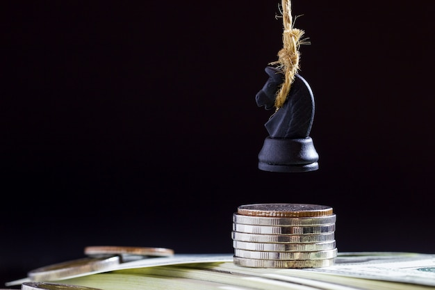 Horse or king of chess execute by hanging on dollar banknote and coin in darkness background.