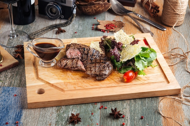 Horse meat steak with sauce on the wooden board