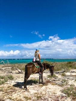 Horse riding tourists in cuba. girl on a horse on a beach.