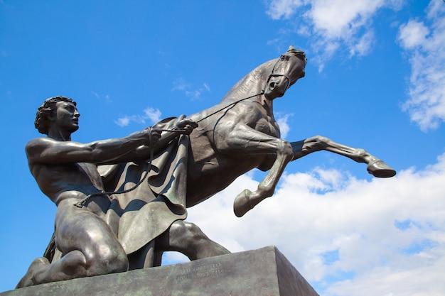 Скульптура укротителя лошадей петра клодта (1851 г.) на аничковом мосту в санкт-петербурге, россия. ориентир