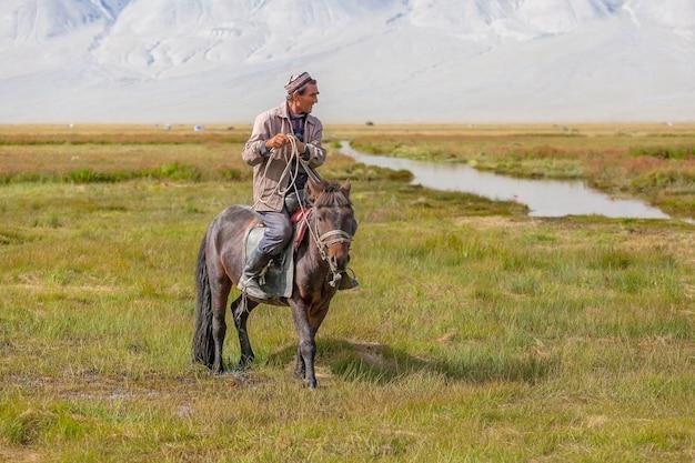 Верховая езда в монгольском пейзаже. алтай, вид на монгольскую долину