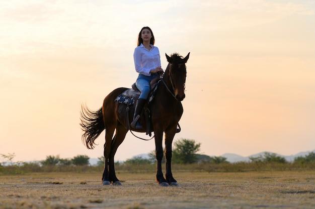Верховая езда сзади с видом на широкое открытое поле и горы