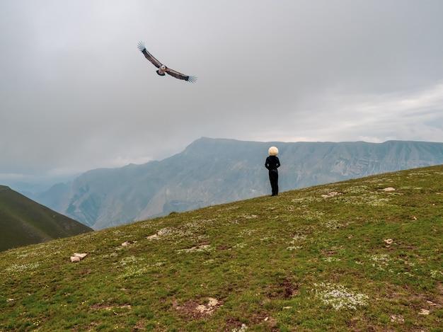 白い帽子をかぶった騎手と高山を背景に飛ぶワシ。ダゲスタン