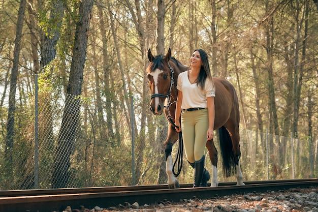 鉄道に沿って馬と一緒に歩く騎手