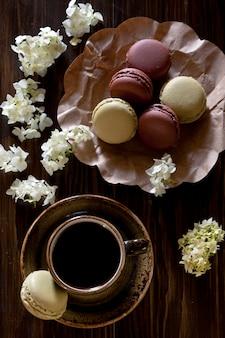 Красочные французские миндальные печенья, и чашка кофе окруженная цветками hortensia на деревенском коричневом деревянном. вид сверху, крупный план