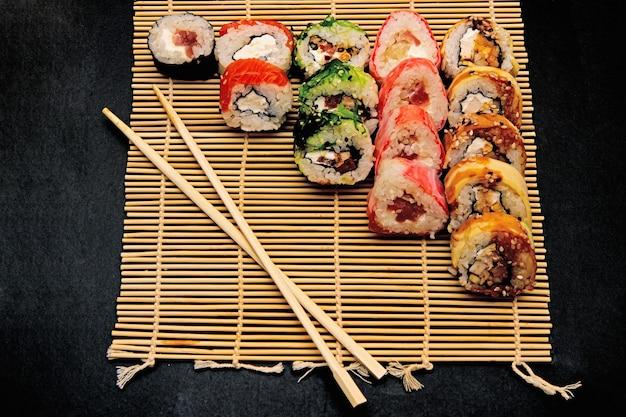 Hosomaki, futomaki and uramaki on bamboo mate with chopsticks on a black surface