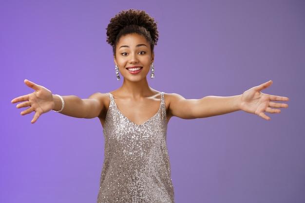 親切で思いやりのある魅力的な若いアフリカ系アメリカ人女性のスタイリッシュなイブニングドレスは、ゲストを招待して腕を伸ばし、抱きしめる抱擁を抱きしめ、笑顔で触れて喜んで歓迎ジェスチャー青い背景を抱きしめます。
