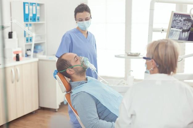 歯科医院の口腔病学の椅子に座って歯科手術の前に酸素マスクを置く病院の助手