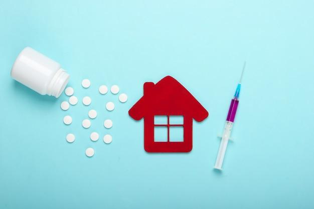 青の背景に病院の建物の置物、注射器、ボトルの丸薬。予防接種。上面図
