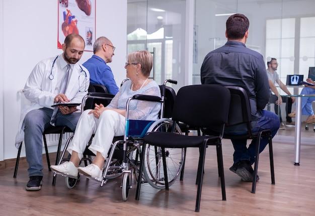휠체어 엑스레이에서 고위 여성과 의사 소통하는 흰 코트의 병원 의사