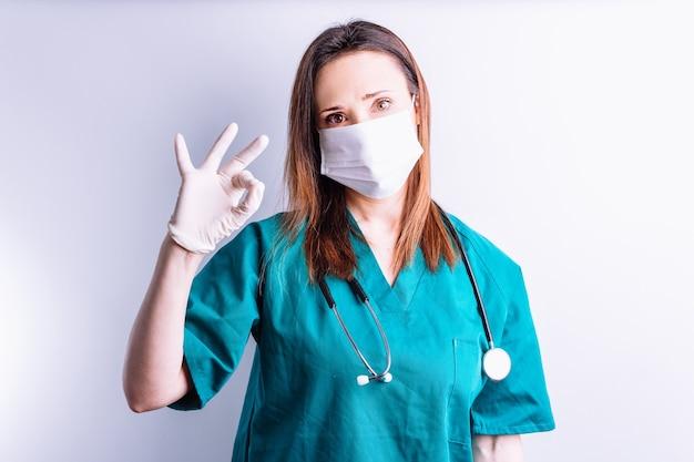 Врач больницы на белом фоне со стетоскопом на шее и маской для лица, делающей руками символ ок