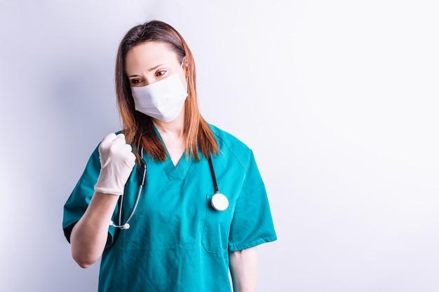 청진기 얼굴 마스크와 장갑을 낀 병원 의사 외과의사는 승리나 좋은 결과의 상징으로 주먹을 꽉 쥐고 있습니다. 외과 의학 개념