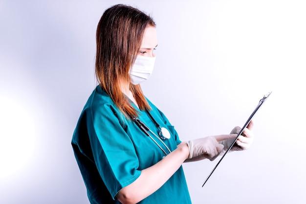 Врач больницы с перчатками маски на белом фоне, читая полный отчет медицины