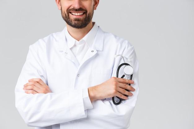 Больница, медицинские работники, концепция лечения covid-19. обрезанный снимок бородатого улыбающегося доктора в белых халатах, скрестив руки, как профессиональный врач или терапевт, держащего стетоскоп.