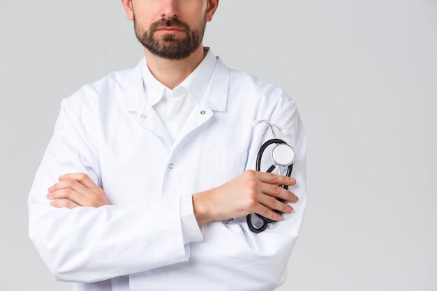 Больница, медицинские работники, концепция лечения covid-19. обрезанный снимок серьезного, уверенного в себе врача с бородой в белых халатах. врач скрестить руки на груди, держа стетоскоп.