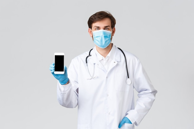 病院、医療従事者、covid-19治療の概念。自己検疫中にクリニックに連絡するための患者のスマートフォンアプリケーションを示す医療マスク、スクラブ、手袋でハンサムな医者を笑っています。