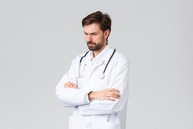 병원, 의료 종사자, covid-19 치료 개념. 문제가 심각해 보이고 걱정스러운 의사가 수술복을 입고 어려운 결정에 직면하고 문제의 사건을 해결하고 눈살을 찌푸리며 숙고합니다.