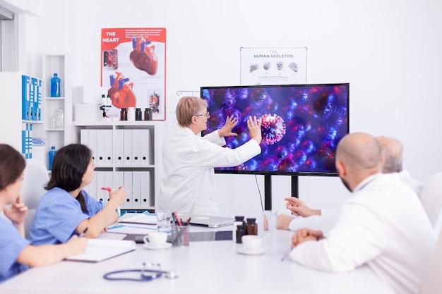 병원 팀은 회의실에서 회의 중 코로나바이러스에 대해 논의합니다. virolog 전문 의사는 위험한 바이러스, 증상으로 인한 세계적 유행병에 대해 동료들과 논의합니다.