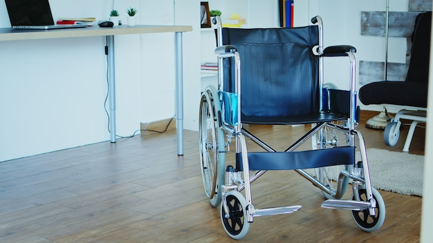 Hospital wheelchair in empty room for helping people with handicap move.
