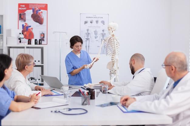 医療の専門知識を議論する体の解剖学の骨格を使用して骨の構造をプレスティングする病院の女性看護師。健康診断を説明する医療治療の会議室で働く医師チーム