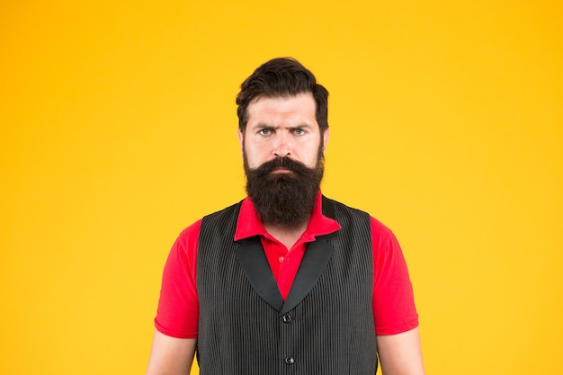 Hospitality staff. restaurant cafe staff wanted. man bearded hipster with mustache wear vest and shirt uniform yellow background. shop staff concept. salesman cashier career. hiring shop store worker.