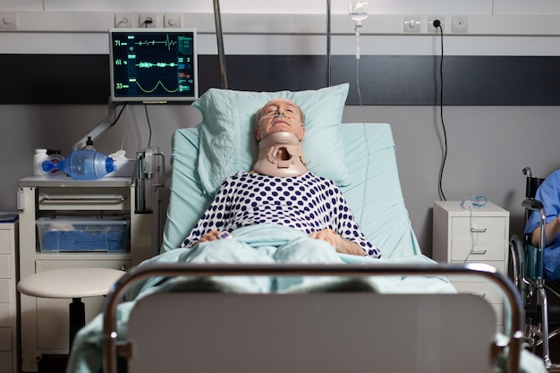 Hospitalized senior laying unconscious in hospital room bed wearing neck brace collar having serious health injury, breathing through oxygen mask with intensive pain