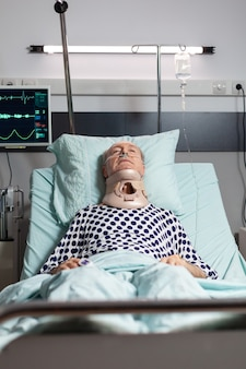 Hospitalized senior laying unconscious in hospital room bed wearing neck brace collar having serious health injury, breathing through oxygen mask with intensive pain.