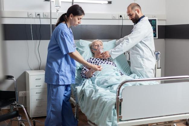 입원한 노인 여성은 병원 침대 의료 간호사에 누워 있는 산소 마스크를 통해 숨을 들이쉬고 내쉬고 있습니다...