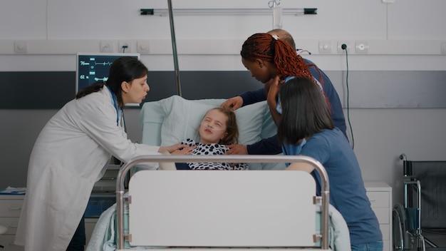 병원에 입원한 아픈 아이가 병 검진을 받는 동안 의료팀이 그녀를 안고 있는 동안 통증 발작을 겪고 있습니다...