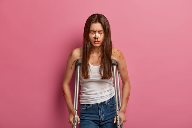 Hospitilized woman has rehabilitation period after serious accident, various fractures, poses on crutches, suffers from serious spine disease, injured after car crash, has broken bleeding nose