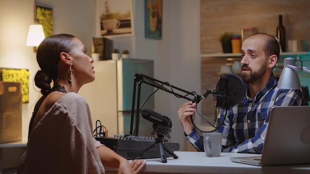 Ospite e ospite che parlano durante il podcast sul microfono in home studio. spettacolo online creativo produzione in onda trasmissione su internet host in streaming di contenuti live, registrazione di comunicazioni sui social media digitali