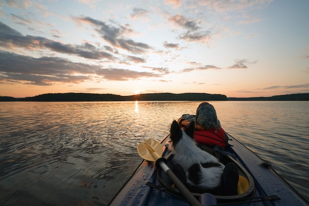 The hostess and the dog are sailing on the lake in a kayak boat at sunset