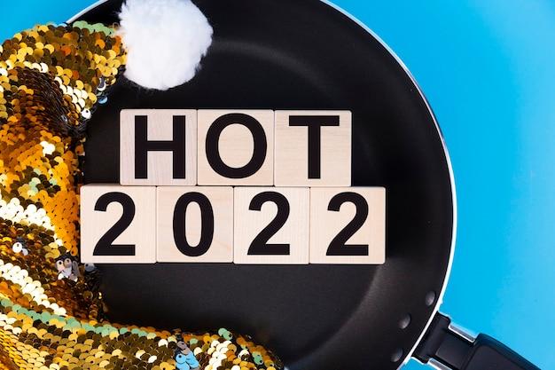 Hot 2022新年の数字は、フライパンとサンタクロースの帽子の上にある木製の立方体に書かれています。