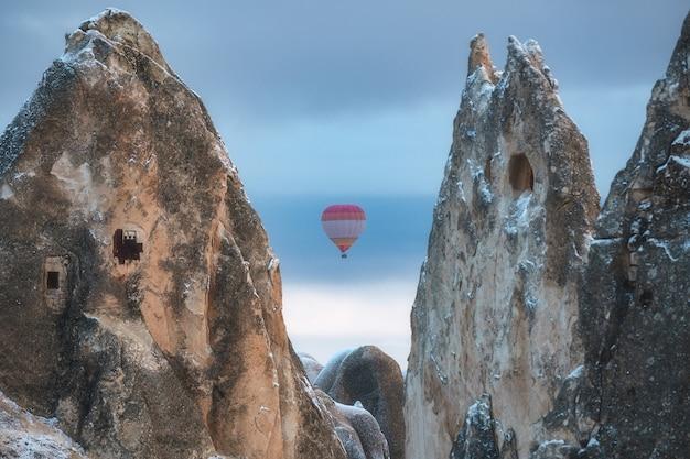 Hot air balloon flies between rocks