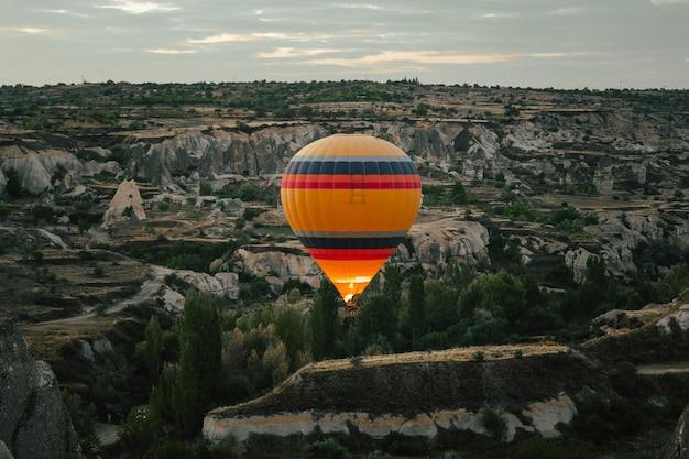 Hot air balloon flying over cappadocia at dawn