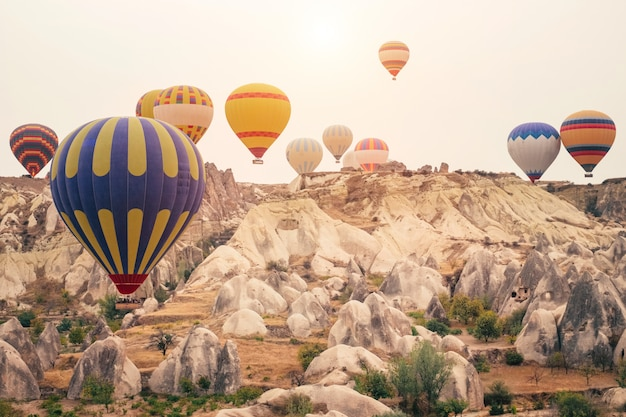 Hot air balloon flying over cappadocia mountain landscape at gold sunrise