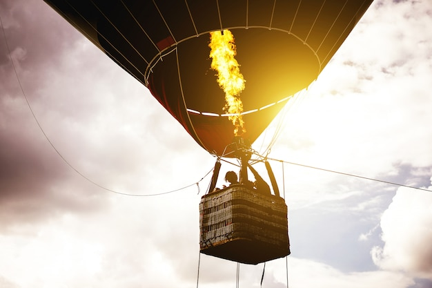 Hot air balloon flying in a cloudy sky at sunrise