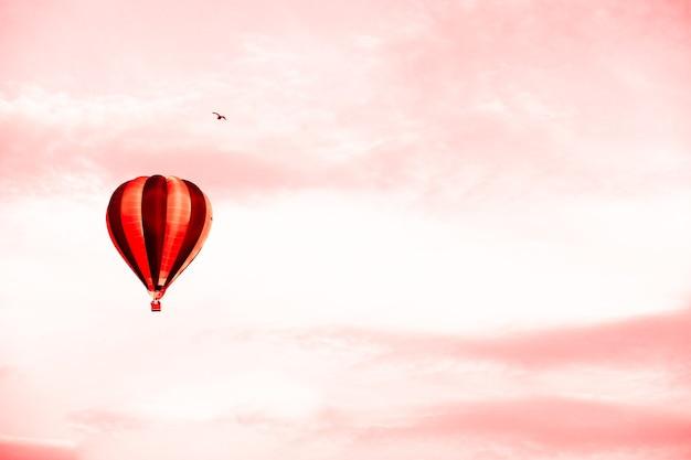 コピースペースと夏の日没の赤い空の熱気球。航空便による商品の配送の概念