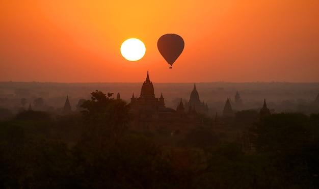 ミャンマーの霧の朝のバガンの平原上の熱気球
