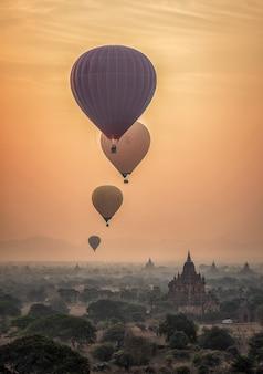 霧の深い朝、ミャンマーのバガンの平野に熱気球