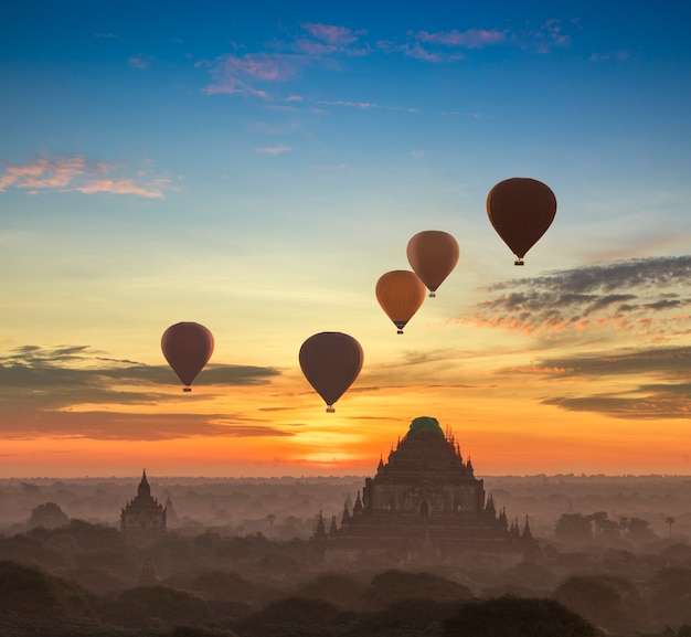 Hot air balloon over plain of bagan in misty morning, myanmar at sunrise.