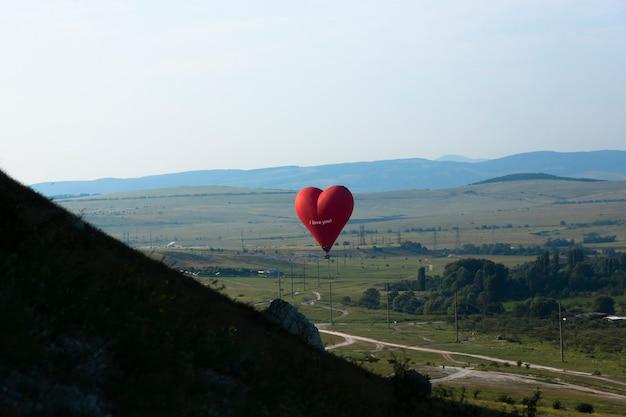 熱気球、ホワイトロックを背景に空飛ぶハートの形をした赤い風船。高品質の写真