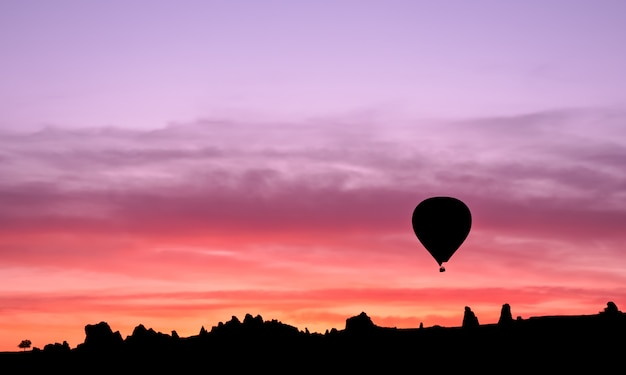 Hot air balloon silhouette in mountains at sunrise, goreme, cappadocia, turkey