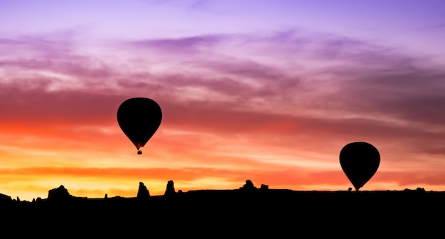 Hot air balloon silhouette in mountains at sunrise