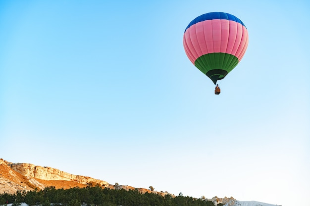 Hot air balloon with basket flying in the sky