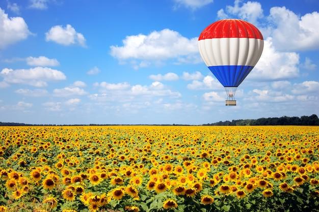 Воздушный шар с флагом франции пролетает над крайним крупным планом поля подсолнухов. 3d рендеринг