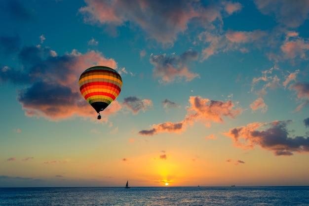 海の背景に夕日と熱気球